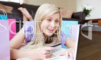 Jolly woman shopping online lying on the floor
