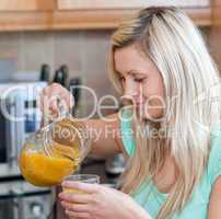 Smiling woman drinking orange juice in a kitchen