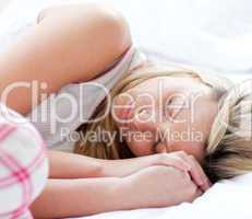 Charming young woman sleeping on a bed