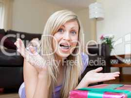 Astonished charming woman opening gifts lying on the floor