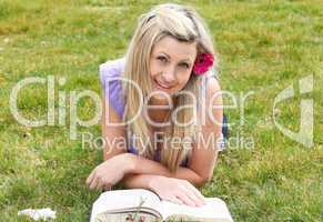 Smiling woman reading a book in a park