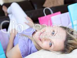 Happy woman after shopping lying on the floor