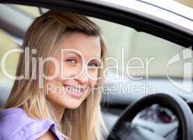 Jolly young female driver sitting in her car
