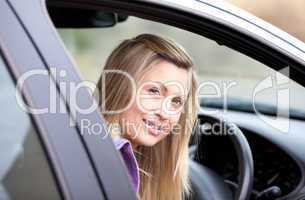Attractive young female driver sitting in her car