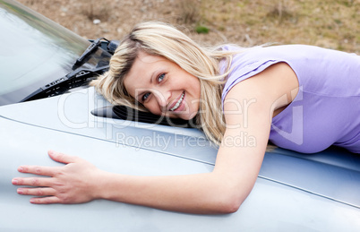 Jolly young driver huging her new car
