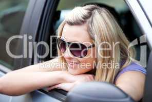 Charming female driver wearing sunglasses in her car