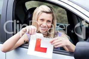 Cheerful young female driver tearing up her L sign