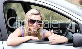 Happy female driver wearing sunglasses with thumb up