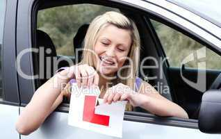 Happy young female driver tearing up her L sign