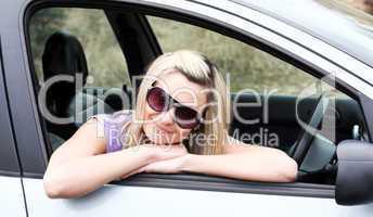 Beautiful young female driver wearing sunglasses