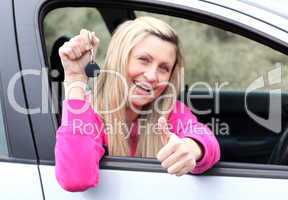 Happy female driver showing a key after bying a new car