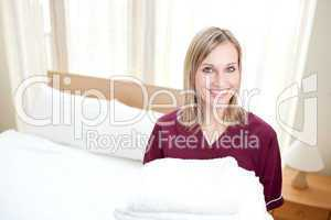 Radiant cleaning lady holding towels in a hotel room