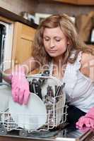 Young woman using a dishwasher