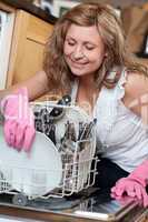 Smiling young woman using a dishwasher