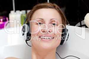 Cheerful woman using headphones in a bubble bath