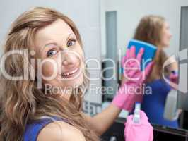 Charming woman cleaning a bathroom's mirror