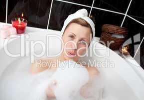 Delighted woman having fun in a bubble bath