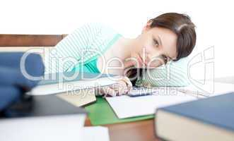 Attractive tired woman studying on a table