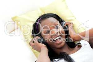 Laughing woman listening music with headphones lying on a sofa