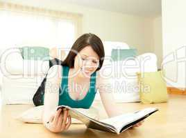 Smiling woman reading a magazine lying down on the floor