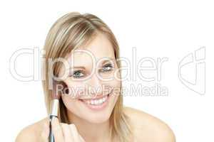 Portrait of a delighted woman using a powder brush