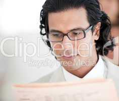 Confident businessman reading a newspaper