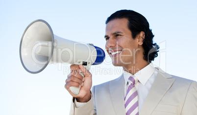 Portrait of a latin business man shouting through a megaphone