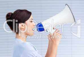 Confident businesswoman yelling through a megaphone