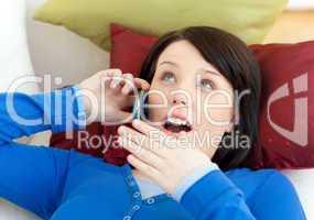 Surprised teen girl talking on phone lying on a sofa