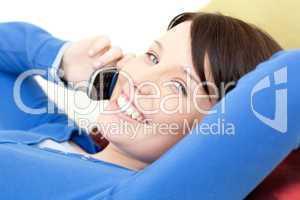 Joyful young woman talking on phone lying on a sofa