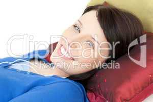 Cheerful young woman listening music lying on a sofa