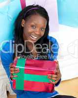 Jolly woman holding a present sitting on the floor