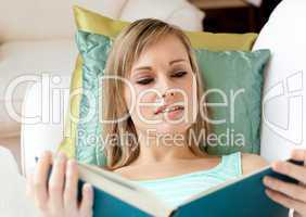 Beautiful woman reading a book lying on a sofa