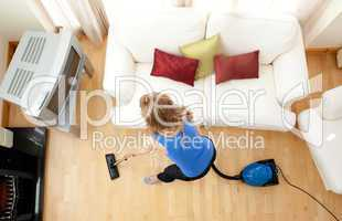 High angle of a blond woman vacuuming