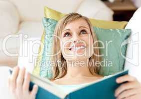 Jolly woman reading a book lying on a sofa