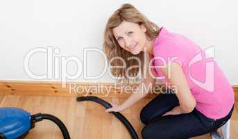 Portrait of a jolly woman vacuuming
