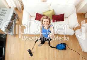 High angle of a cheerful woman vacuuming
