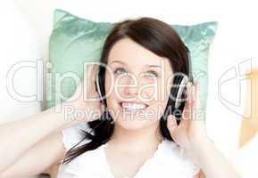 Smiling teen girl listening music lying on a sofa
