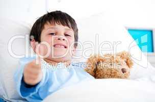Little boy hugging a teddy bear lying in a hospital bed