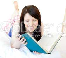 Portrait of a confident teen girl studying lying on a bed
