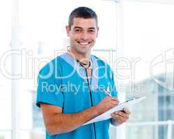 Smiling male doctor making notes on a patient folder