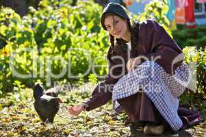 Woman feed chickens
