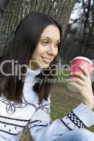 Female in a park drinking coffee