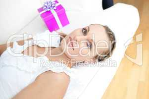 Beautiful blond woman with a present lying on a sofa