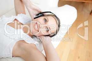 Bright young woman listening music lying on a sofa
