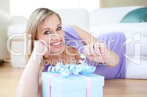 Delighted blond woman holding a present lying on the floor