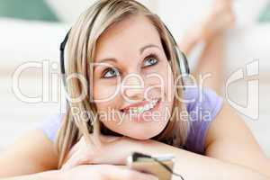 Charming woman listening music lying on the floor