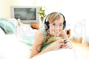 Cheerful blond woman listening music lying on a sofa