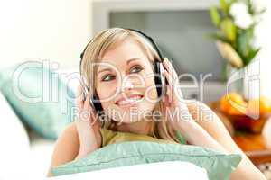Charming blond woman listening music lying on a sofa