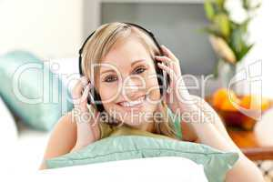 Happy blond woman listening music lying on a sofa